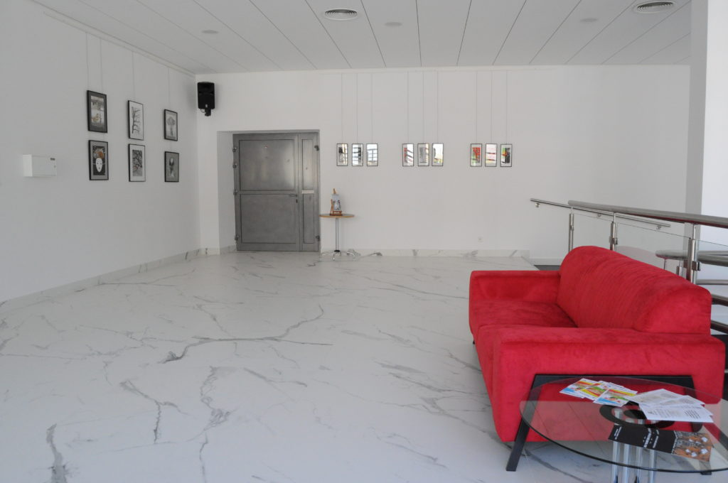 Hol boczny. Na pierwszym planie znajduje się stolik szklany, kawałek dalej kanapa czerwona, a w tle na dwóch prostopadłych do siebie ścianach wiszą obrazy.