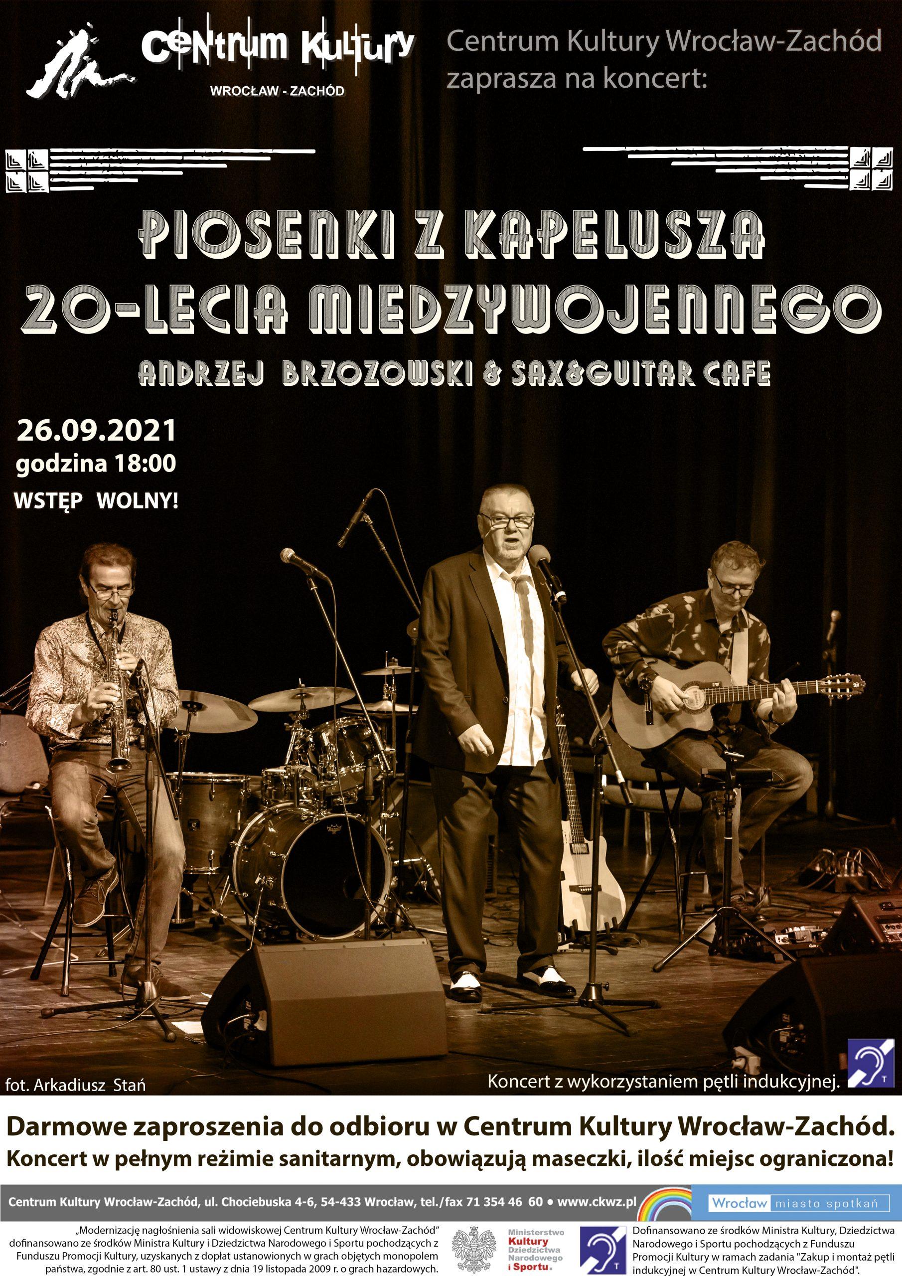 Plakat - piosenki z kapelusza 20-lecia międzywojennego. Andrzej Brzozowski i Sax&Giutar Cafe. 26 września 2021 godzina 18:00. Wstęp wolny za zaproszeniami dostępnymi w dziale programowym CKWZ. Na plakacie widnieje zespół grający na scenie, od lewej saksofonista w środku Andrzej Brzozowski przed mikrofonem i z prawej gitarzysta grający na siedząco. Koncert w pełnym reżimie sanitarnym, obowiązują maseczki, ilość miejsc ograniczona.